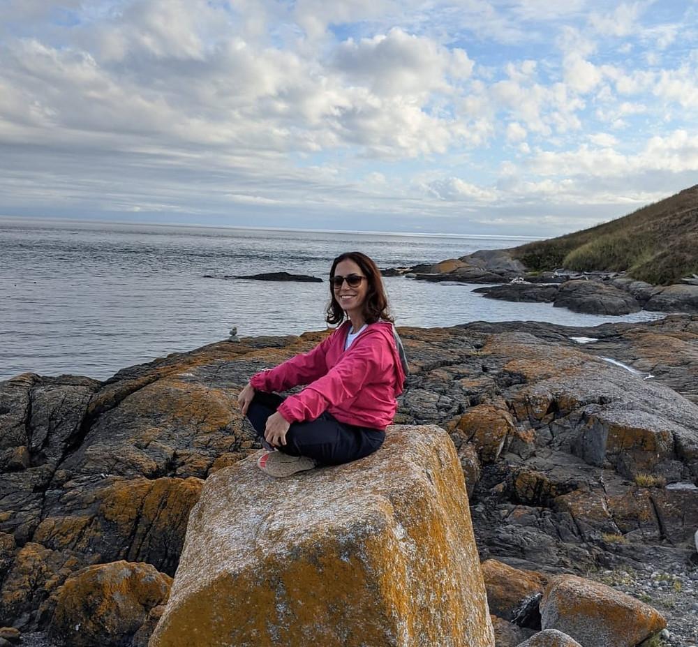 אישה יושבת על אבן ומשקיפה על האוקינוס