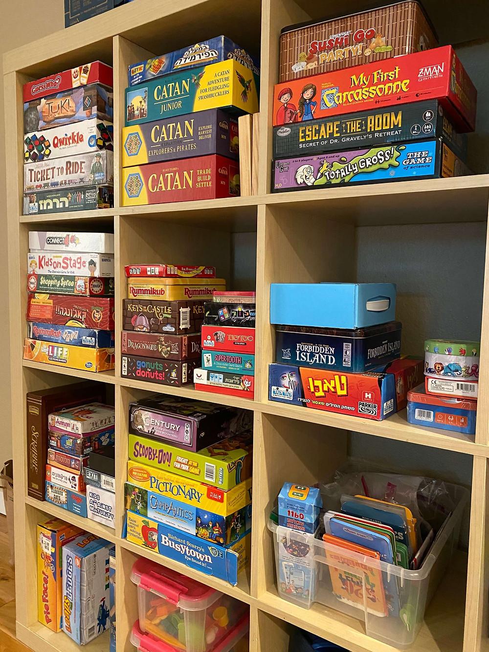 כוננית מלאה במשחקי קופסא בעברית ובאנגלית
