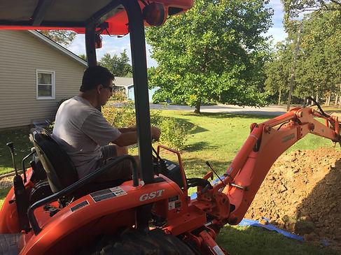 Owner operating orange backhoe