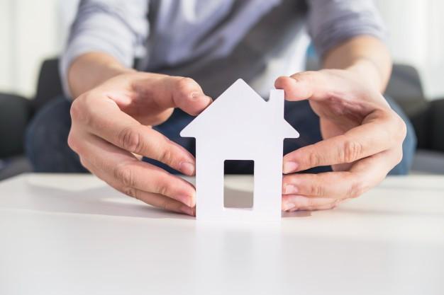 mãos segurando casa