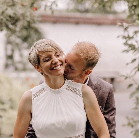 Hochzeitsfotograf Schweiz- Bräutigam küsst Braut am Hals Braut lacht-Boho style