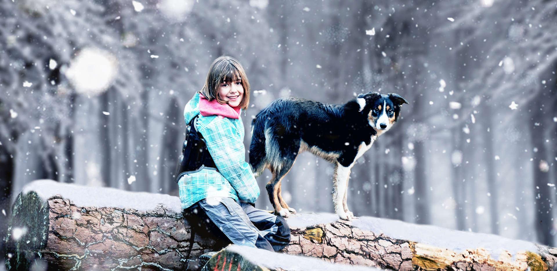 Mädchen mit Hund im verschneiten Wald- Familienfotografie Zentralschweiz