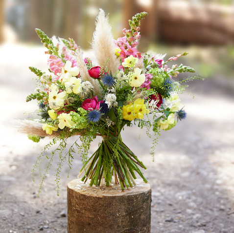 Produktfotografie Blumenstrauss-Blumenstrauss steht auf einem Holzrugel im Wald