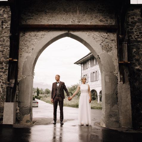 Hochzeitsfotograf Luzern-Brautpaar steht händehaltend unter Torbogen