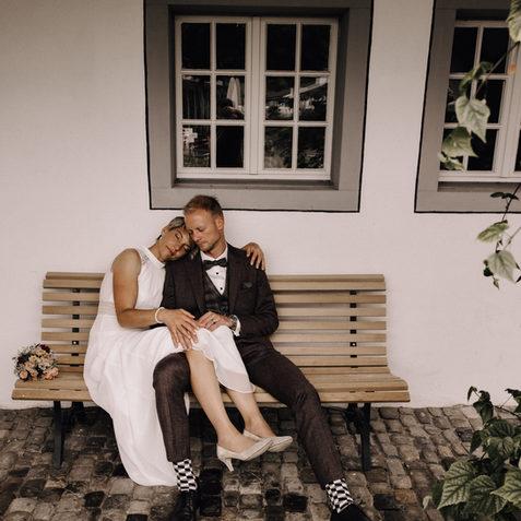 Hochzeitsfotograf Schweiz Luzern-Brautpaar sitzt verträumt auf Bank-Boho style