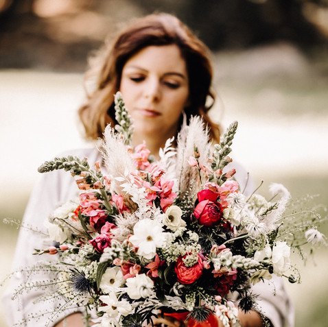 Business Fotografie-Produktfotografie Blumenstrauss- Frau hält grossen Blumenstrauss vor sich und schaut ih n an