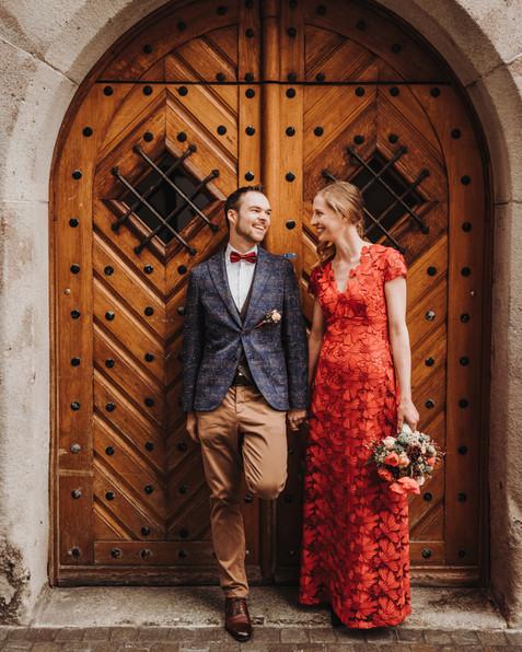 Brautpaar steht vor einer alten Holztüre und schaut sich an-Rathaus Luzern