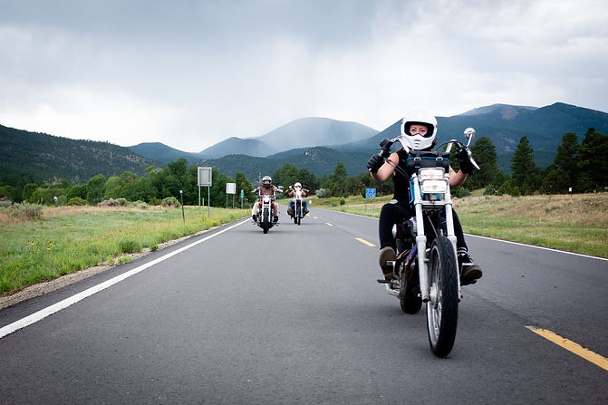 A white motorcycle being ridden down the road by a person in a white helmet. Mountains in background
