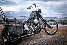 A single black motorcycle, propped up on its kickstand. Mountains can be seen in the distance.