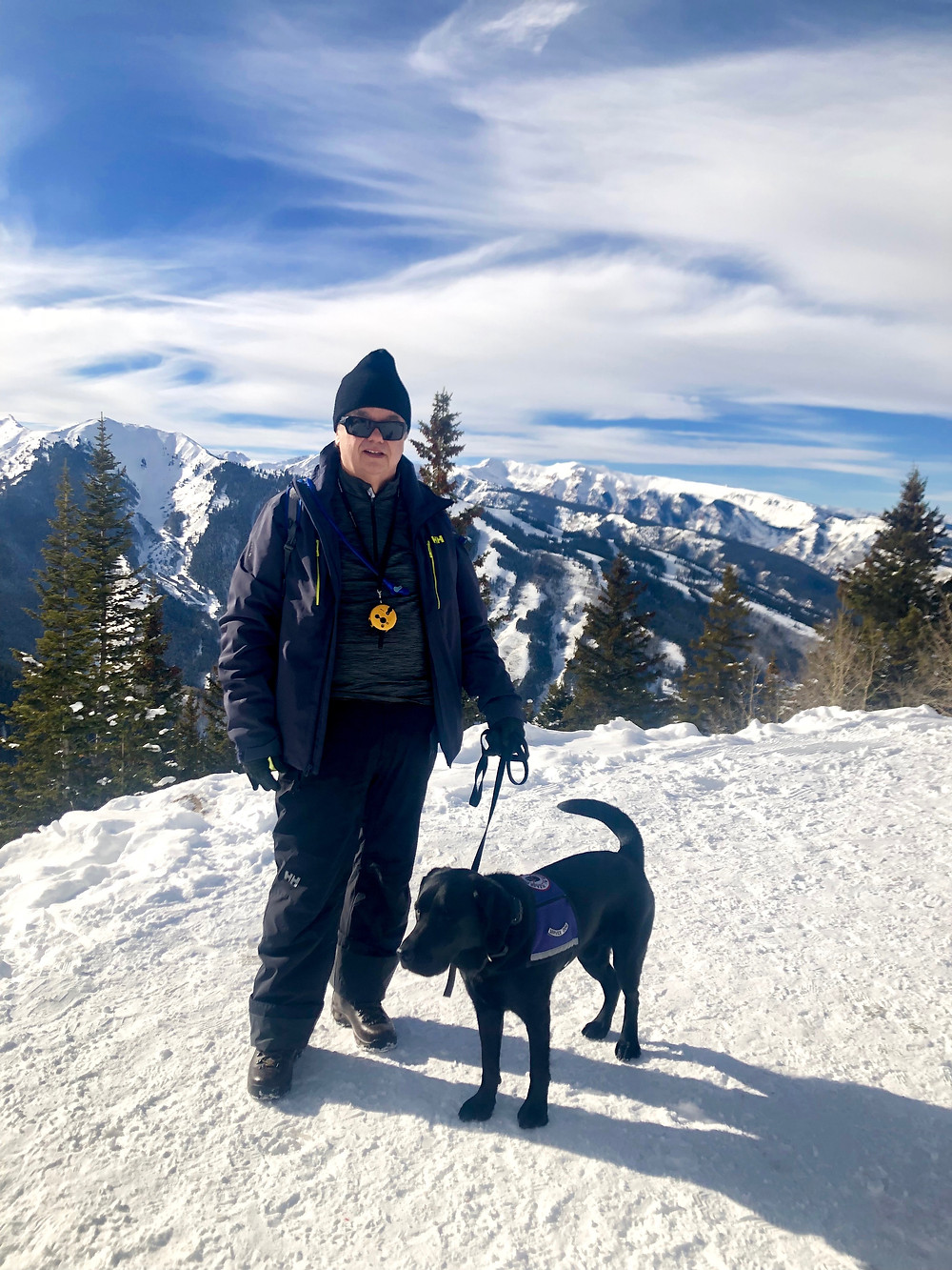 Tim Collins and Ebby his black lab service dog are on a hike near a waterfall.
