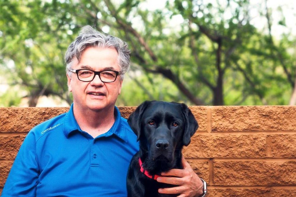Tim Collins sits in a blue polo shirt next to his service dog, black lab, Ebby on their backyard porch.