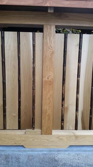 板塀の板の間に黒竹