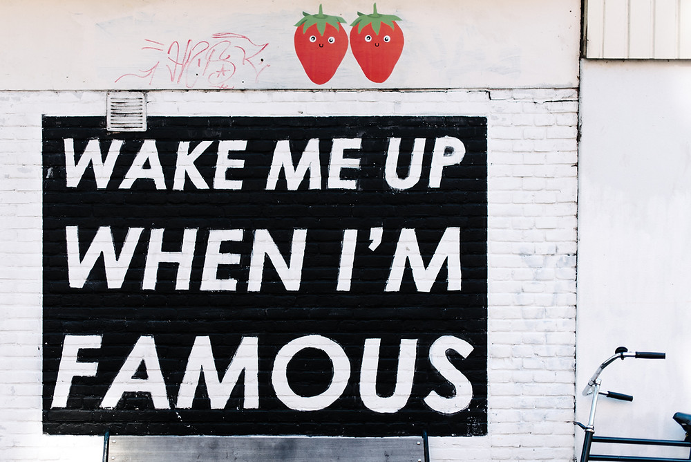 wake me up when im famous quote painted on white wall with two red strawberry illustrations