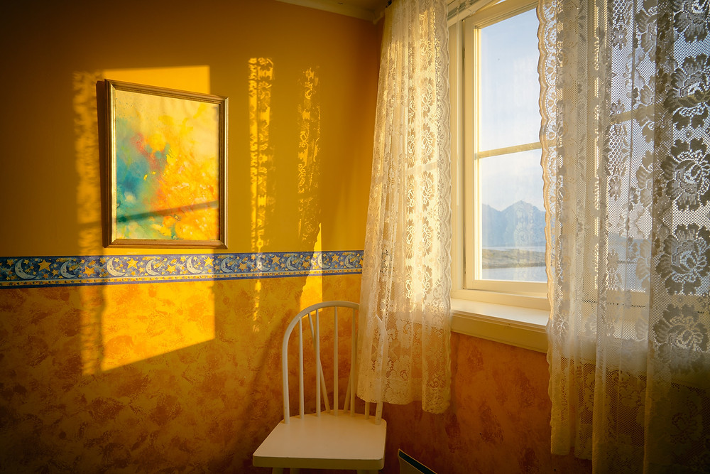 sun shining on corner of yellow bedroom with lace curtains at window
