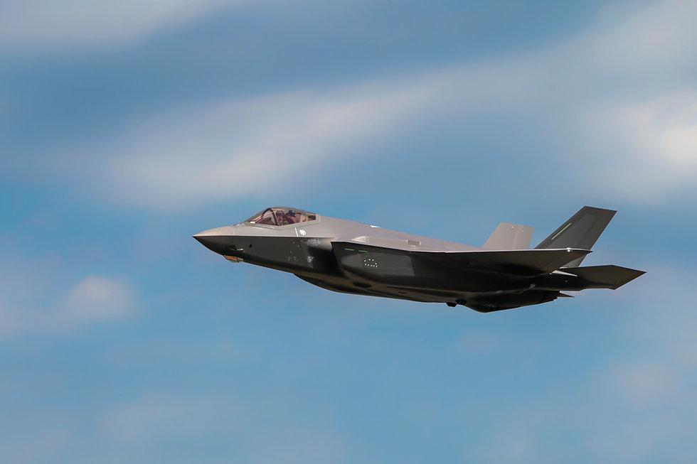 Military F35 fighter jet flying. Blue sk