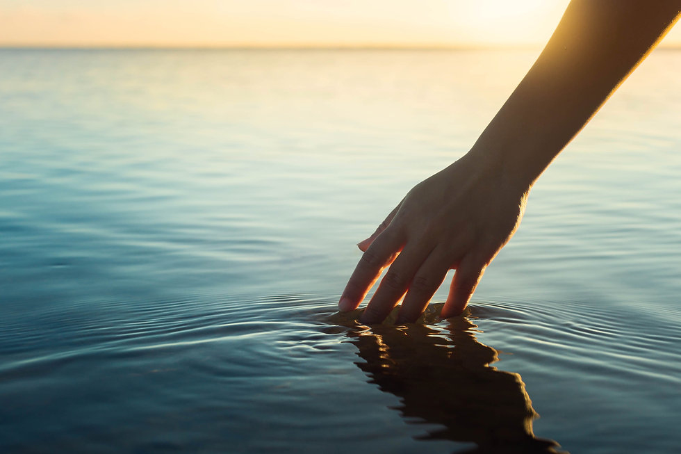 A female hand touching the ocean water in front of a beautful sunset during summer time..j