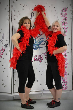 two adult tappers with red boas