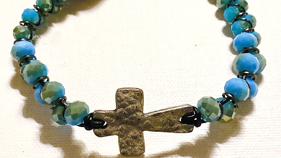 Antiqued hammered gold cross with blue crystal dangle