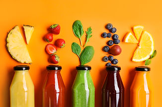 Flat lay composition with bottles of delicious juices and fresh ingredients on orange back
