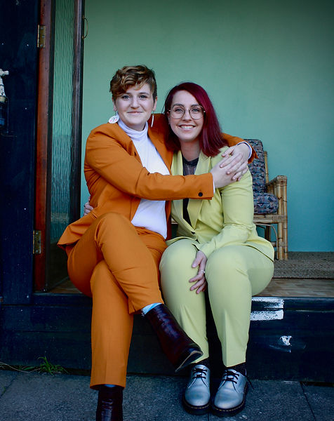 Lou is in an orange suit with their arms around Arlene, in a green suit, sitting in a doorway.