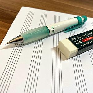 Notenblatt mit Bleistift und Radiergummi