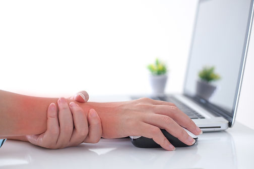 Woman holding her wrist pain from using computer.,Hand pain.jpg