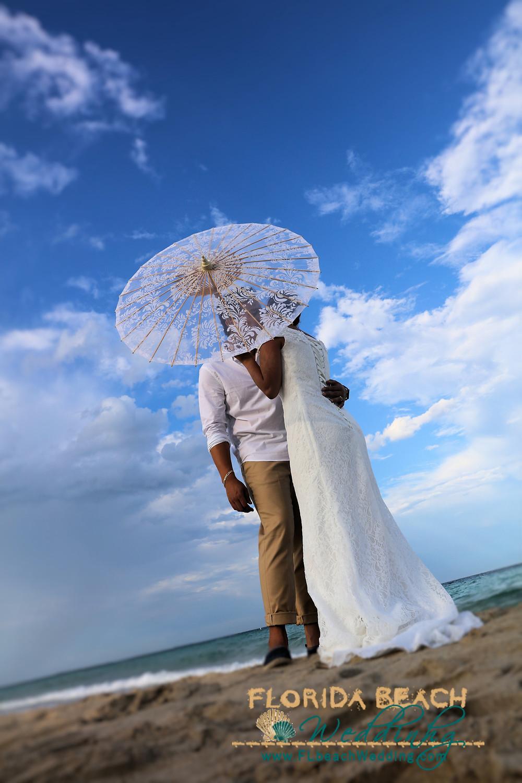 Florida Beach Wedding bride and groom with parasol.