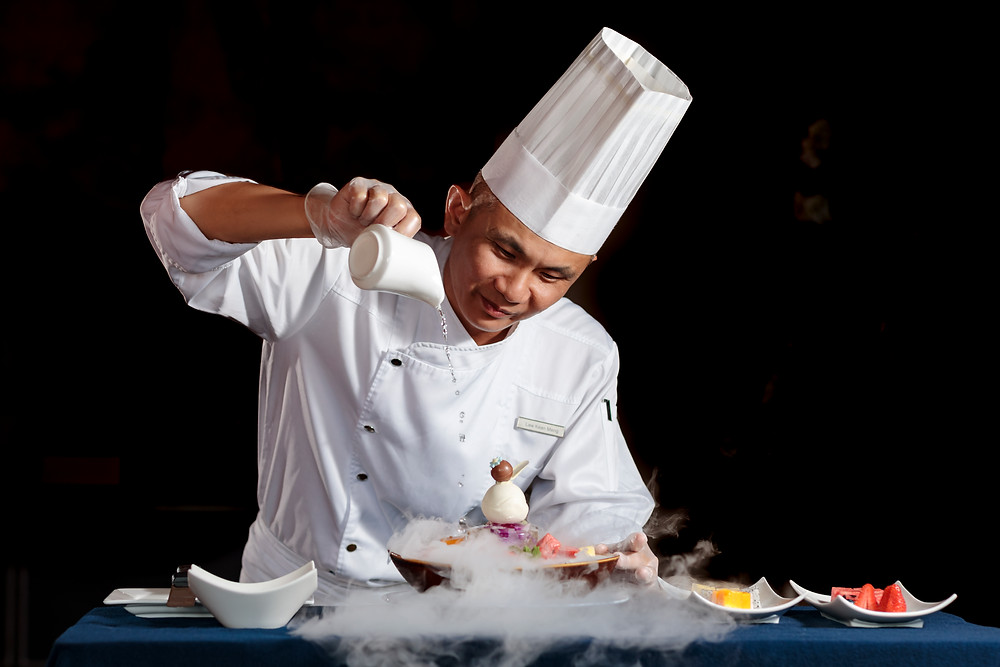 Chef pouring hot water over dry ice dessert