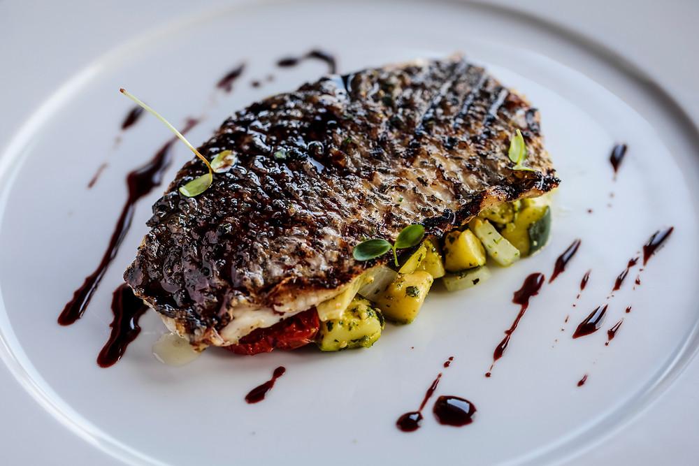 Fish fillet with grilled vegetables (on vegetable bed)