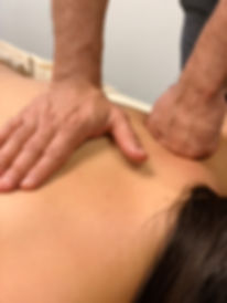 Two hands doing deep tissue massage on a girl's back