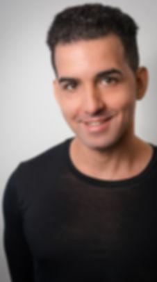 A man in black shirt is smiling- Adam Cardona