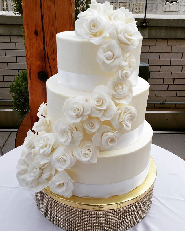 White on white wedding cake with handmade flowers