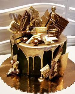 Black and gold drip cake with assorted c