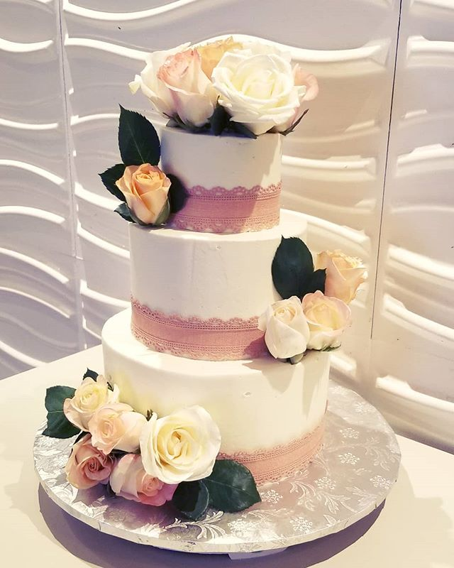 Buttercream wedding cake with pink and p