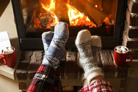 Couple in pajamas resting near fireplace