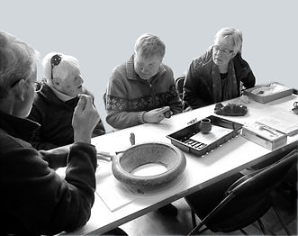 Image of a 4 adults during a object handling session at the museum.