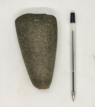 Image of a stone tool with a pen in the