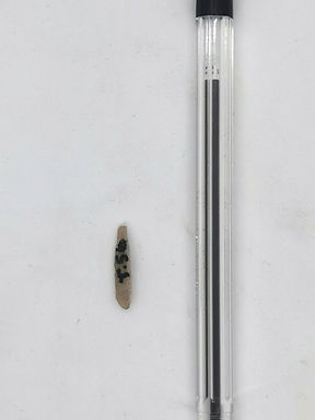 Photograph of a small stone tool. The to