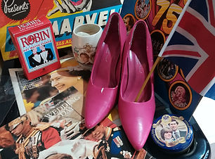 An image of the content of the 1970's to1980's loan box. The image shows a pink pair of womens heeled shoes, a variety of royal memorabila and some Robin brand sor clothestarch f