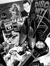 Image of the content of the museums 1970's - 1980's loan box. The image shows a pair of womens shoes, royal memorabila and a pack of robin brand hot water starch
