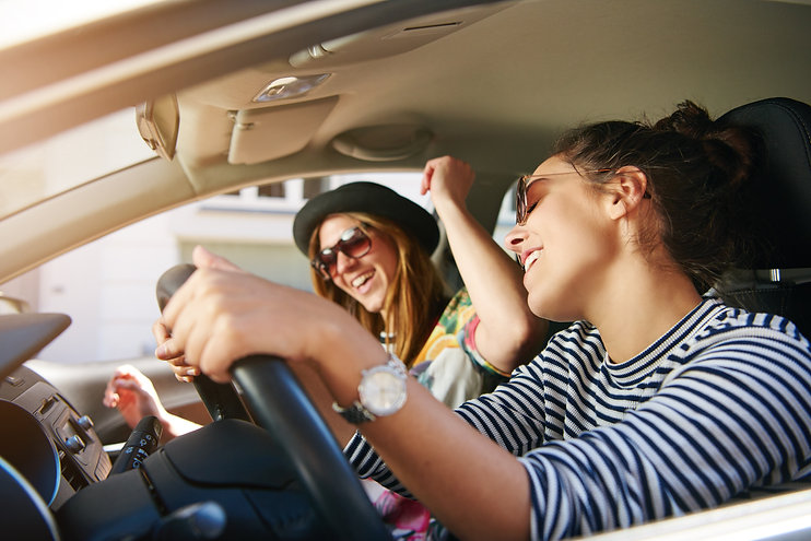 two-young-woman-singing-along-in-the-car