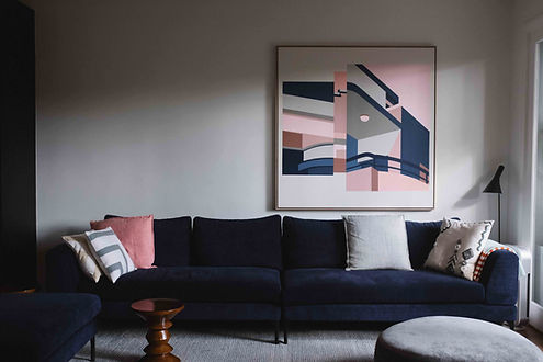 Large pink and navy abstract artwork by ar–chive hangs behind navy couch in a calm living room