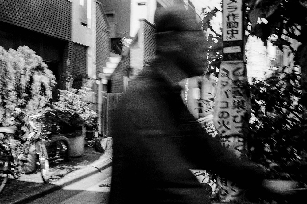 Black and white film photo: Japanese man rides past on bicycle as blurry figure