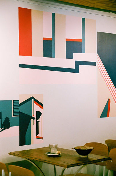 Cafe view at Coolmac: red, pink and navy graphic mural by ar–chive along the wall with wooden seating in front