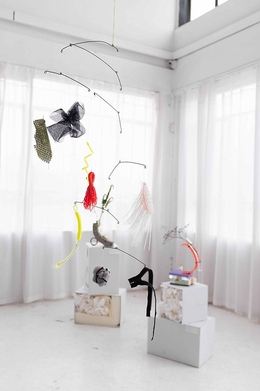 A hanging mobile made of colourful found materials; a zipper, hand cross hatched fabric and yellow coloured perspex tubing
