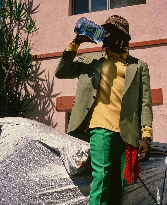 Colourful Editorial photography: IE drinks from his water bottle with pink building and lush palm tree behind him