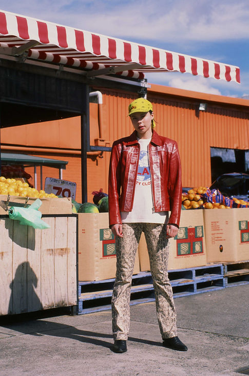 Editorial photography: Female model stands outside fruit shop in red leather jacket and python print pants