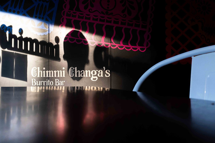 Afternoon light on Chimmi Changa's mural: restaurant name and papel picado with strong shadows