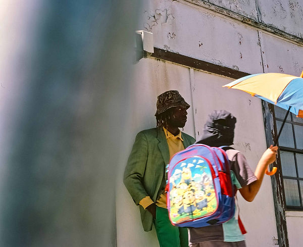 Editorial photography: Model stares off to the side and a child with colourful backpack walks past with umbrella