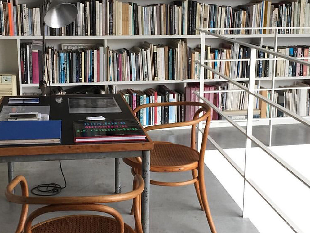 Two chairs and table placed in front of a whole wall of books